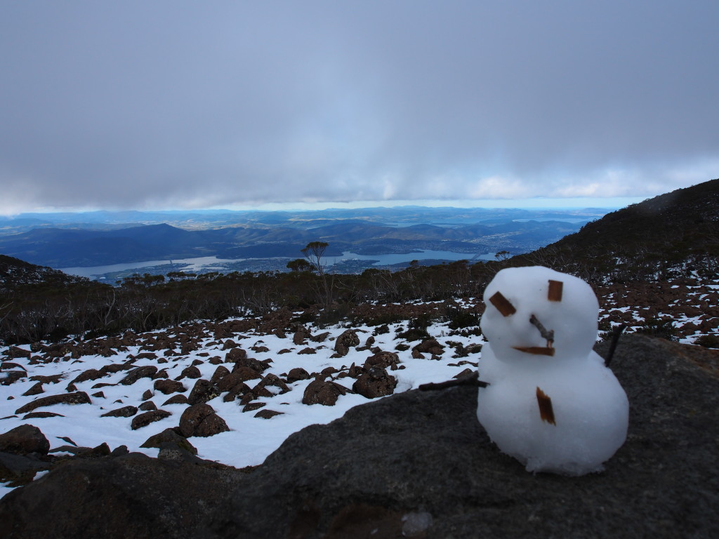 Snowman with the view of the city sandwiched between the clouds and the snow.