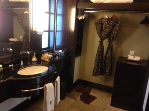 Open closet with bathrobe hanging.