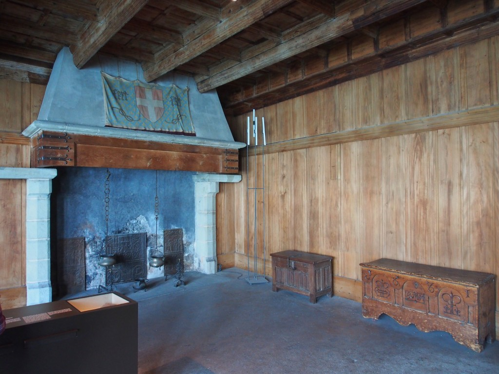 Room with a fireplace and wooden walls.