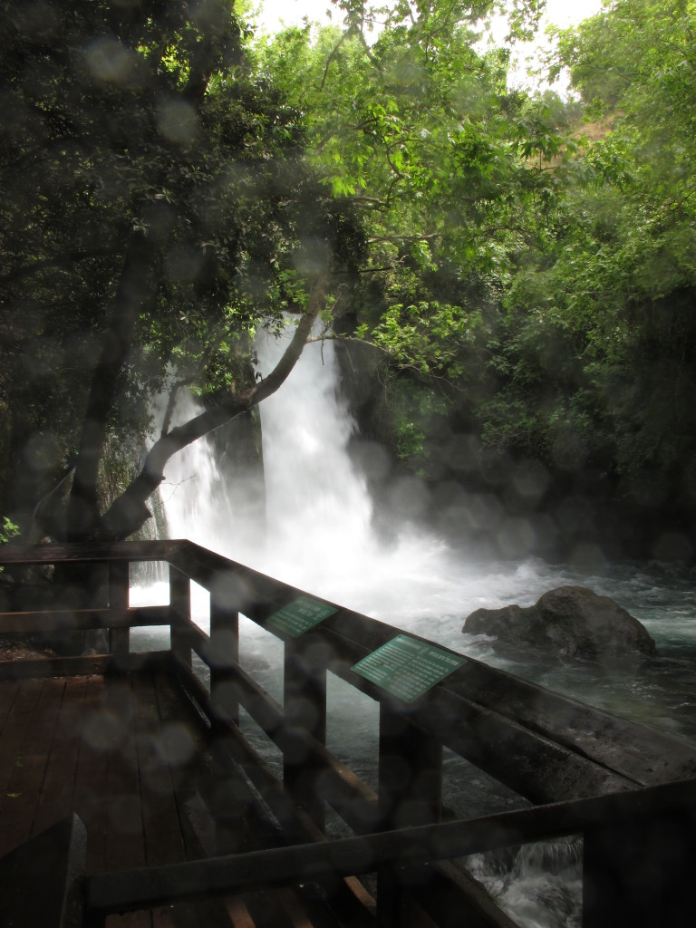 Waterfall furiously flowing, wetting the atmosphere.